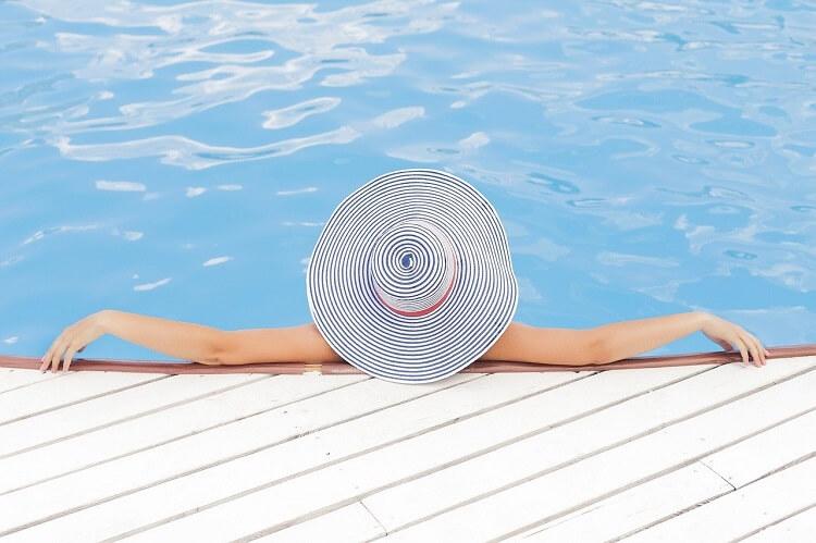 Mulher relaxando na piscina. Uma ótima imagem para empreendimentos de lazer produzir conteúdo na crise causada pela covid-19.